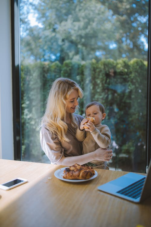 Woman Having Breakfast With her Baby