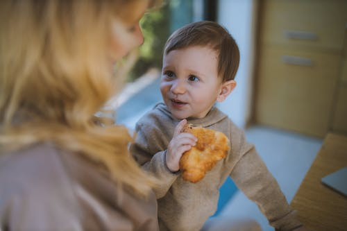 Baby Boy Eating a Croissant With his Mother