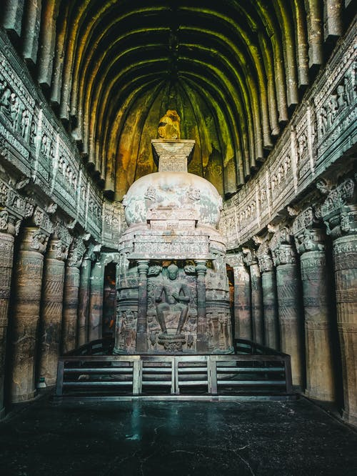 Interior of arched old temple with Buddha statue in middle