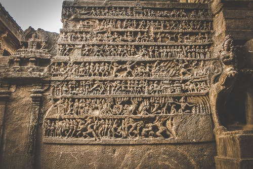Carved pictures on stone wall of ancient temple