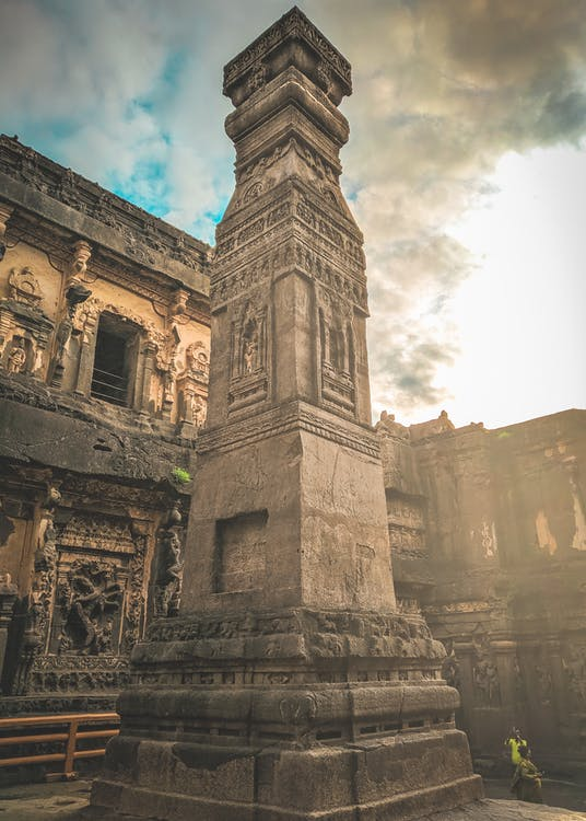 From below of ancient stone monument located in yard of abandoned oriental historical complex against cloudy sky in sunny day