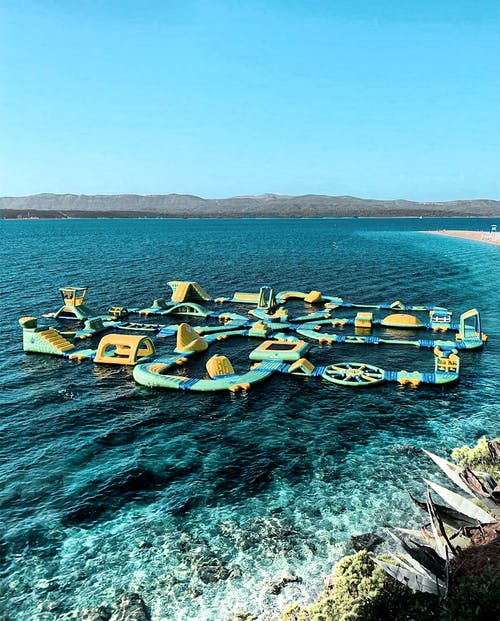 Yellow and Green Floating Water Playground on Blue Sea Under Blue Sky