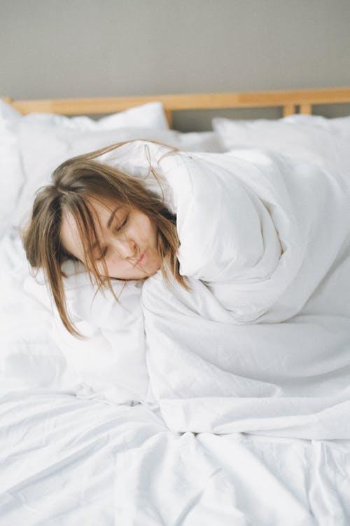 Mulher Coberta Com Manta Branca Deitada Na Cama