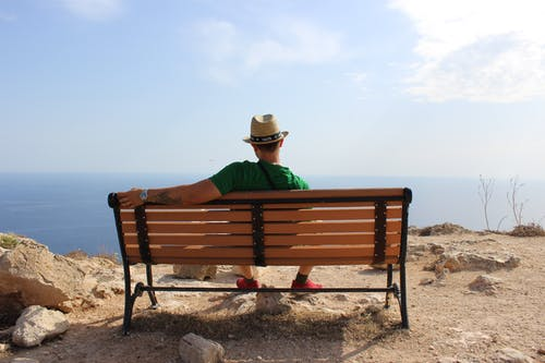 Man in Green Shirt Sitting on Brown Wooden Bench
