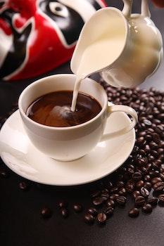 White Ceramic Pitcher With White Cream Pouring on Black Coffee Mug