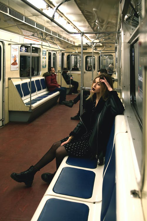 Woman in Black Leather Jacket Sitting on Blue and White Train Seat