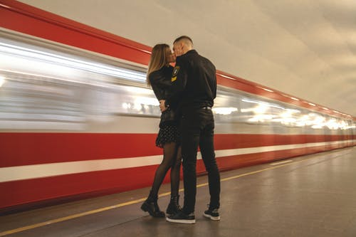 Young couple kissing on platform in underground