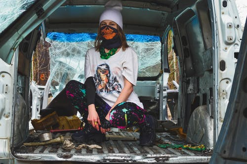 Full body of anonymous female teenager in informal clothes covering face with handkerchief and sitting on haunches in trunk of dirty broken car