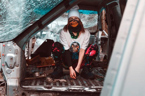 Unrecognizable young female teenager in abandoned car
