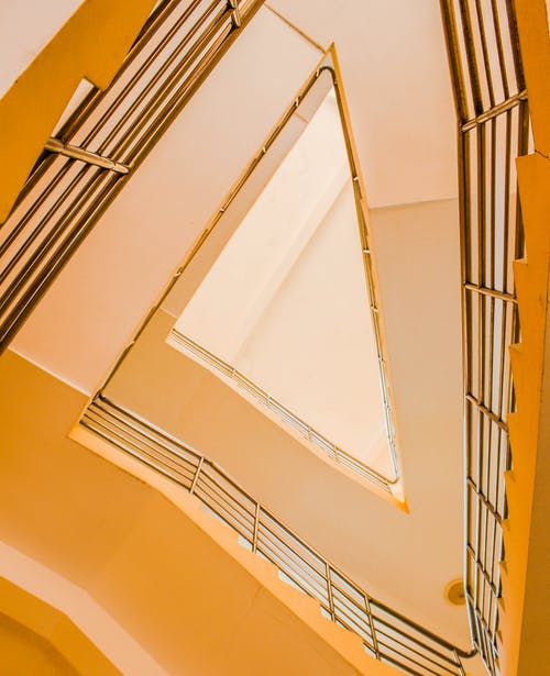 From below of yellow geometric triangle shaped staircase with metal railings inside contemporary building