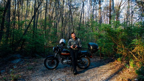 Man With Motorcycle in the Middle of the Forest
