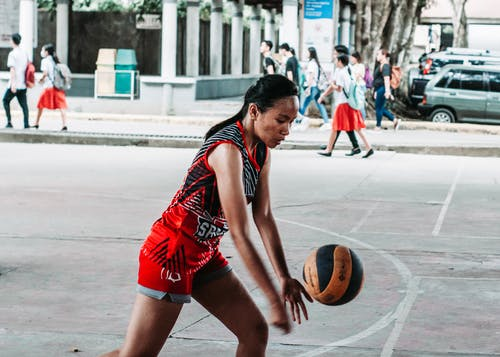 Side view of focused fit young ethnic female athlete in activewear playing volleyball on sports ground in city park