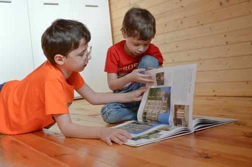 Curious smart little siblings in casual clothes sitting on wooden floor and reading interesting book at home