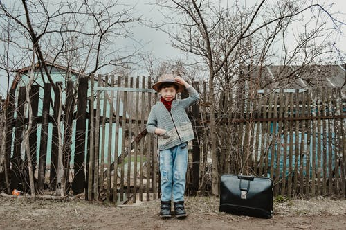 Cheerful child traveler standing on rural path near fence of old cottage