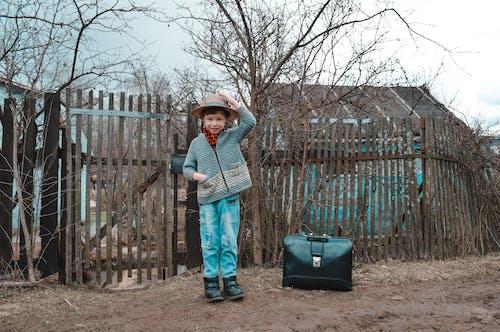Smiling kid adjusting hat in village