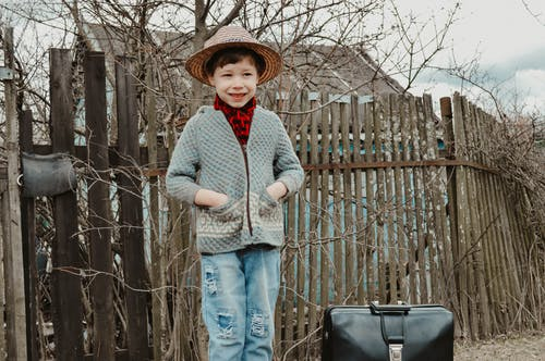 Delighted little child in warm jacket and straw hat standing near wooden fence with hands in pockets and looking away during vacation in village