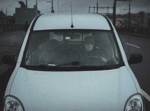 From above of unrecognizable male in medical mask driving white car on street on gloomy cloudy day during coronavirus