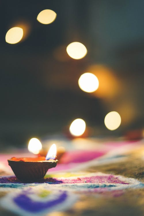 Small burning candle on colorful cloth