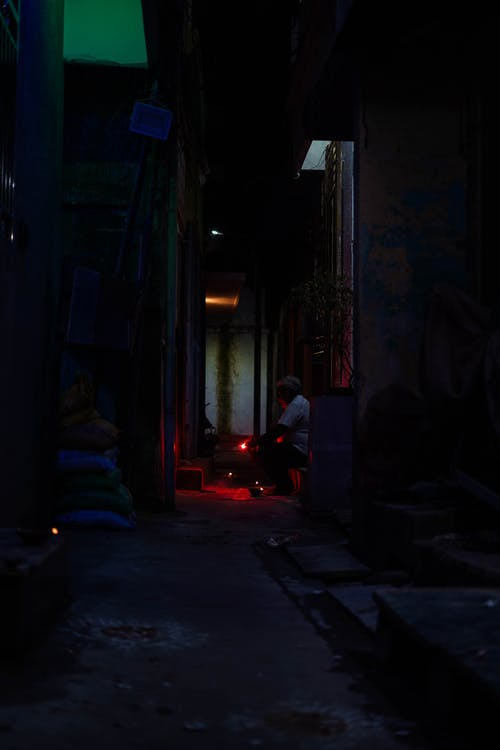 Side view of anonymous people sitting on step in dark yard of old building with burning candles at night