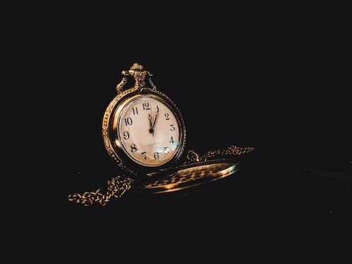 Old fashioned round watch in dark room