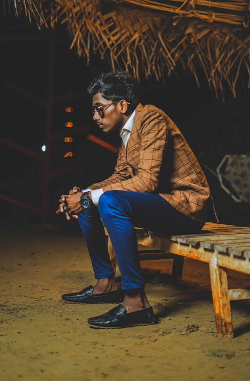 Serious Indian man in modern clothes sitting on bench