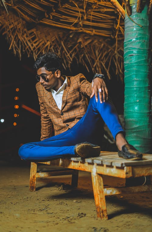Indian man in trendy clothes sitting under palm
