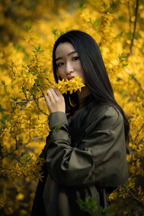 Woman in Black Leather Jacket Holding Yellow Flowers