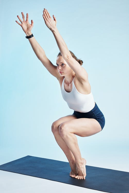Woman in White Tank Top and Blue Shorts Doing Yoga
