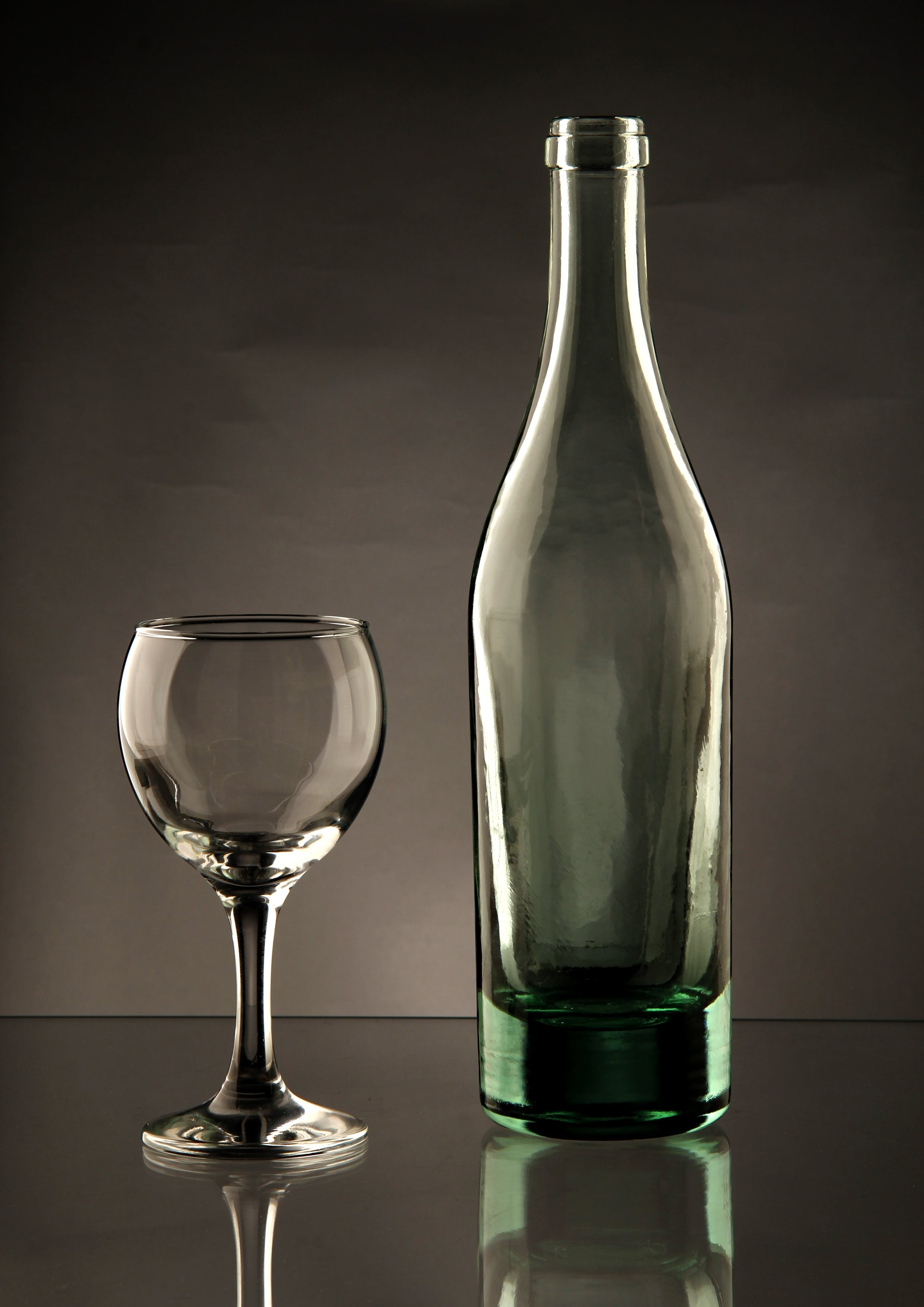 Clear Glass Bottle Beside Wine Glass