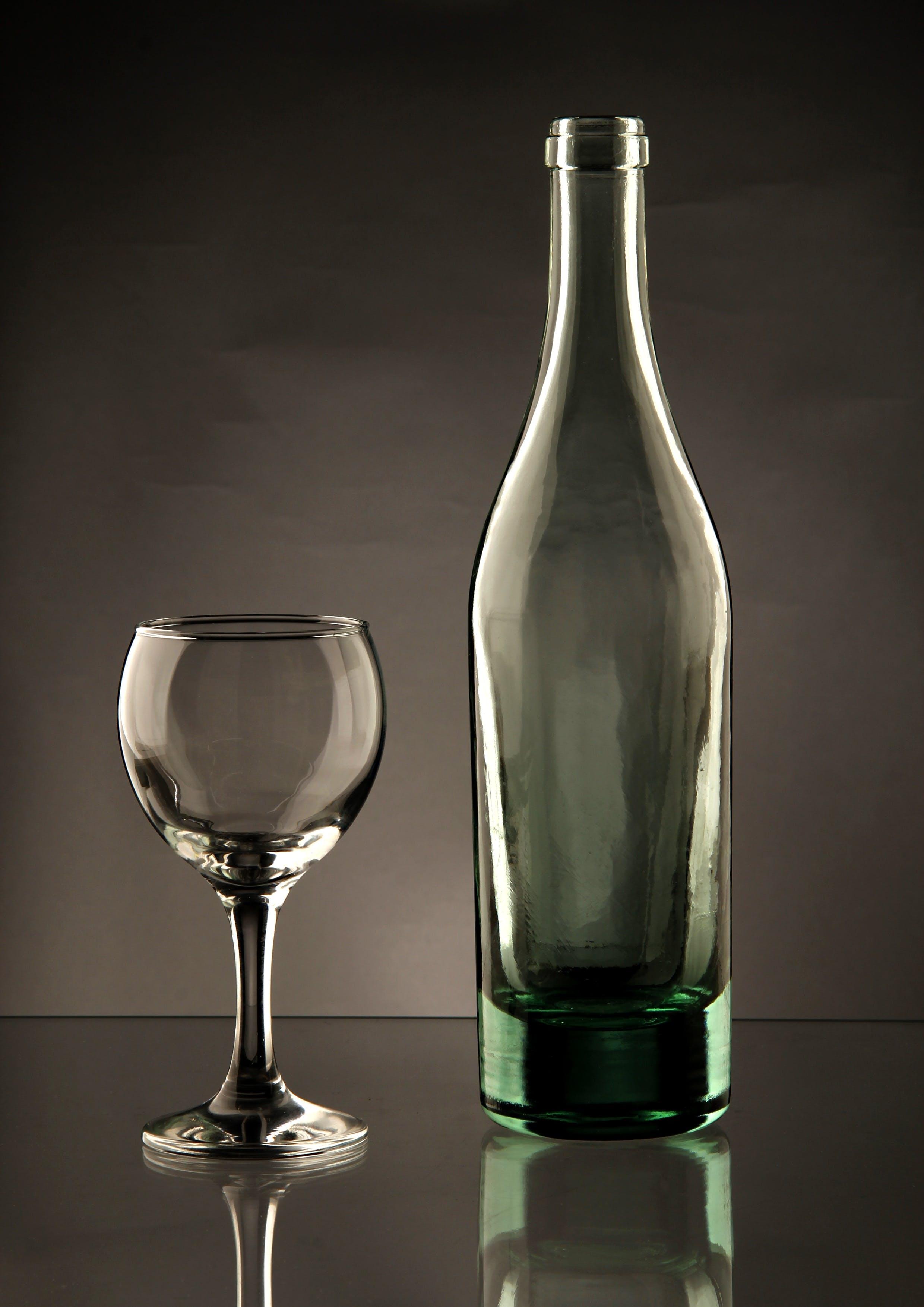 Clear Glass Bottle Beside Wine Glass