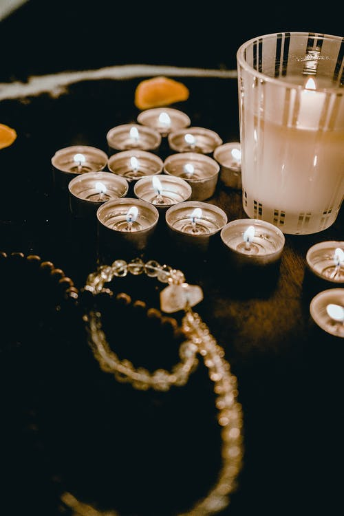 Candle Lights and Necklace on Wooden Table