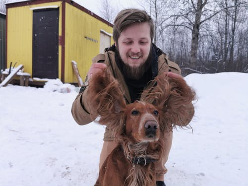 Man in Brown Jacket Holding Brown Dog