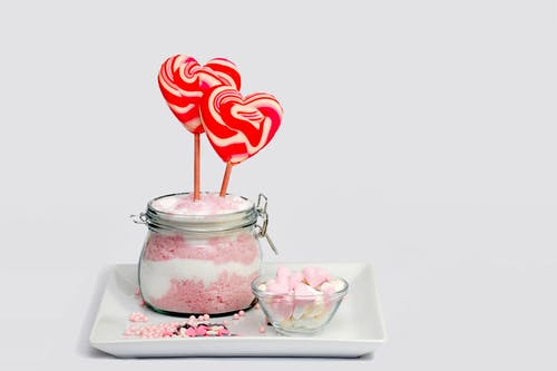 Pink and Grey Heart Shape Lollipop on Clear Glass Jar