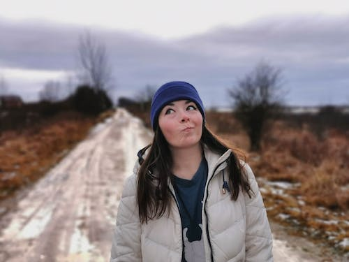 Woman in White Jacket and Blue Knit Cap Standing on Snow Covered Ground