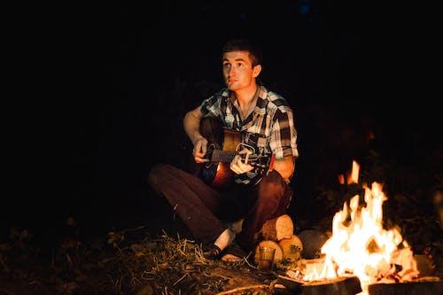 Man Playing Guitar Sitting on Brown Log