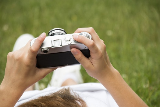 Person in White Dress Holding Grey and Black Camera on Grassland
