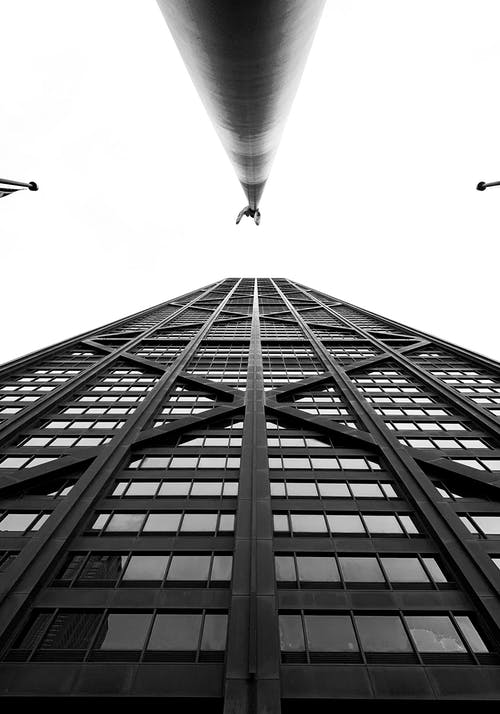 Black and white low angle of modern high tower with reflecting windows located in contemporary city