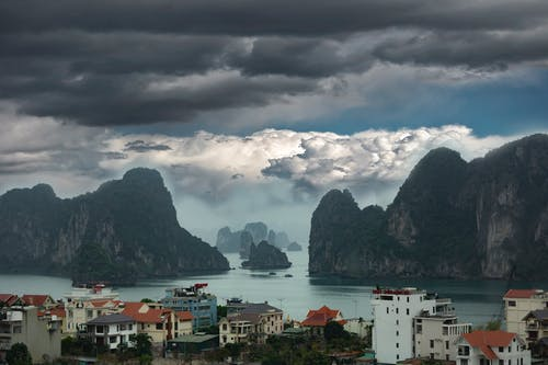 High angle of residential houses and of rocky cliffs covered with green plants in middle of sea under dark stormy sky