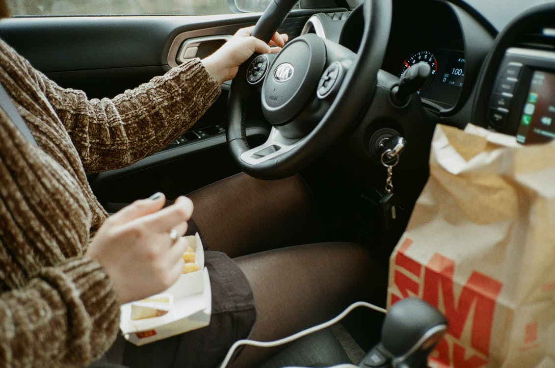 Person in Brown Long Sleeve Shirt Driving and Eating
