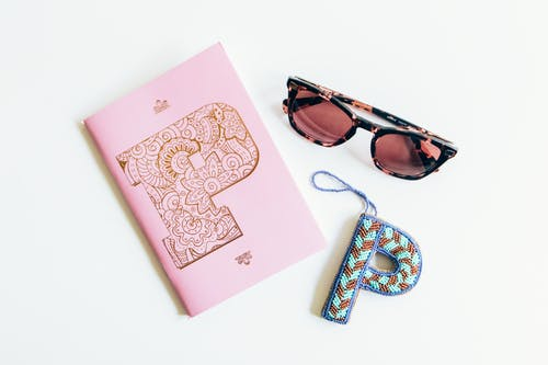 Black Framed Sunglasses Beside Pink Notebook and Letter P Decor