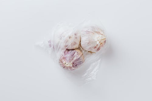 Three Garlic Bulbs Inside Plastic Bags
