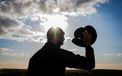 Silhouette of Man Holding a Hat