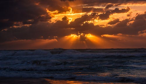 Picturesque bright sunset above wavy endless ocean at night