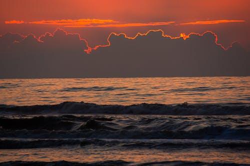 Ocean near mountains under bright red sky at sundown