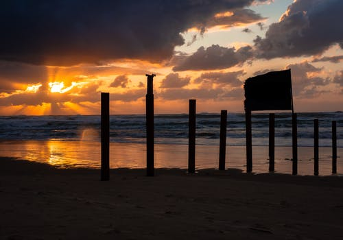 Scenery view of bright sky with clouds illuminated by sun under ocean and coast with wooden fence and signboard at sunset in evening