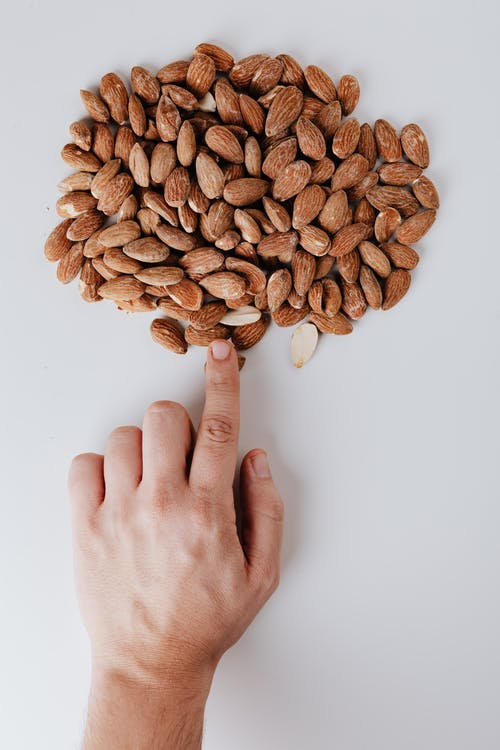 Person Hand Pointing on Almonds