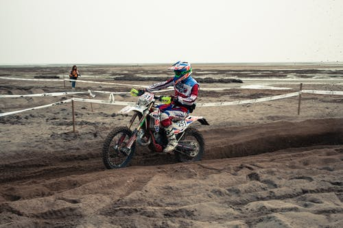 Man Riding Motocross Dirt Bike on Brown Sand