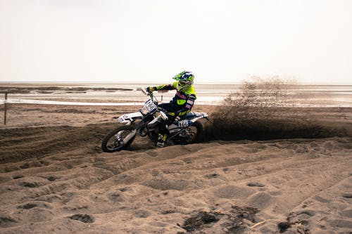 Man in Green and Black Motorcycle Suit Riding Motocross Dirt Bike
