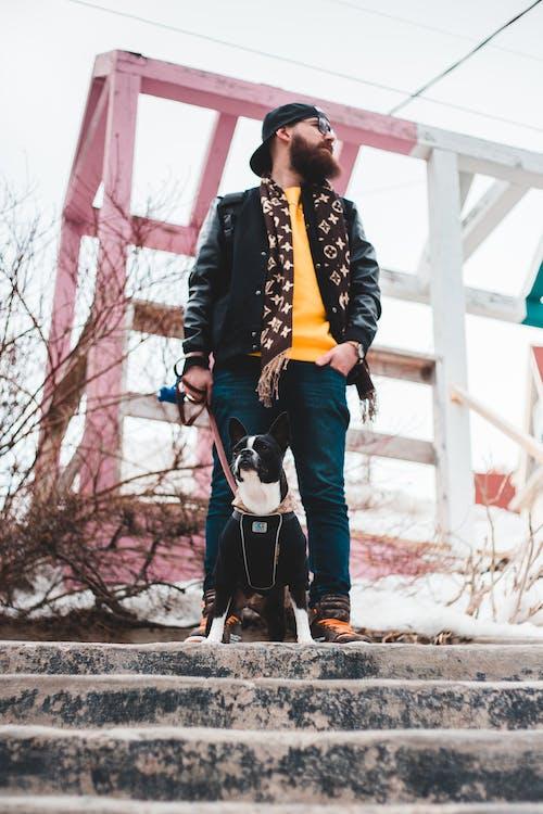 Man in Black Jacket Holding Black and White Short Coated Dog