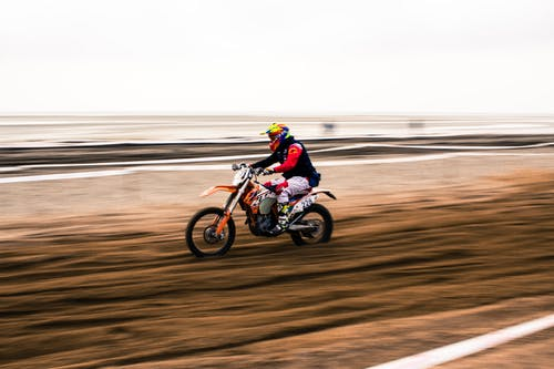 Man Riding Motocross Dirt Bike on Road